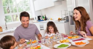 parent family-laughing-around-a-good-meal-in-kitchen