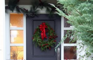decorate Front door with a Christmas wreath and bows