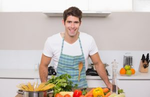 cooking Young man with vegetables standing in the kitchen at home
