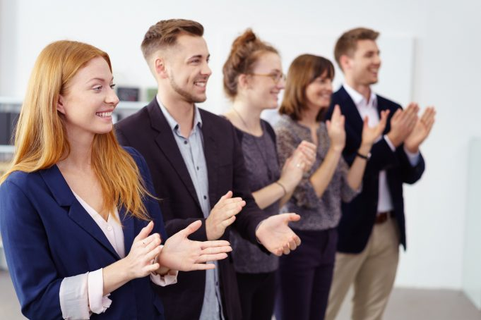 Row of impressed young business co-workers clapping a colleague work