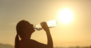 Fitness woman silhouette drinking water from a bottle hydrated