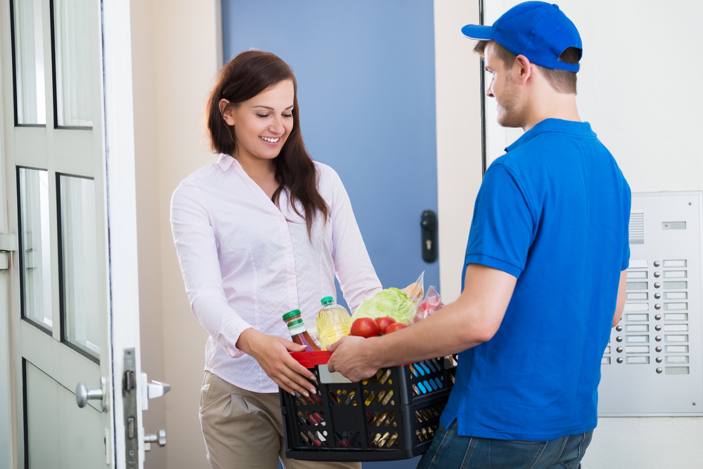 smiling-young-woman-receiving-groceries-delivery