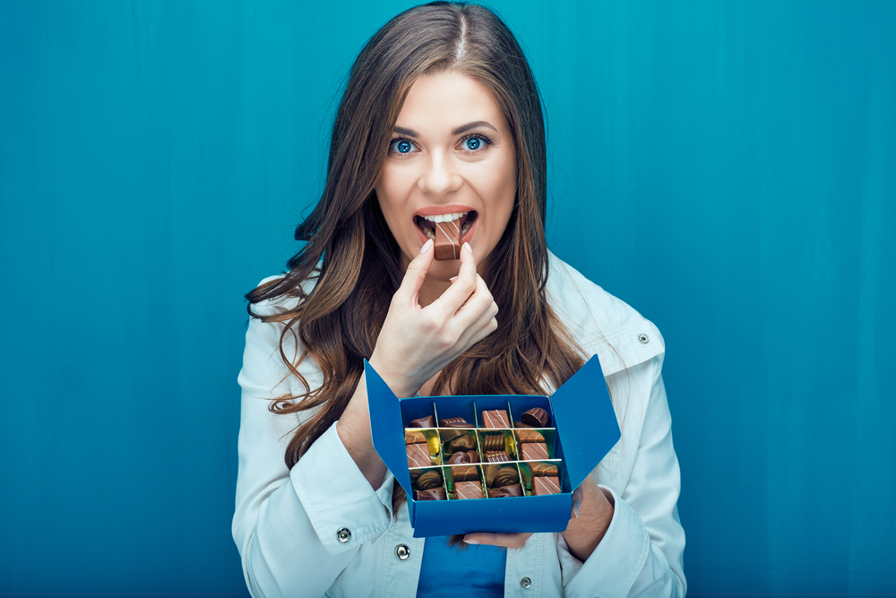 happy-woman-eating-chocolate-candy-portrait