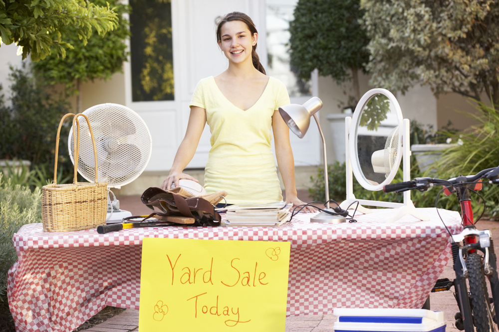 teenage-girl-holding-yard-sale