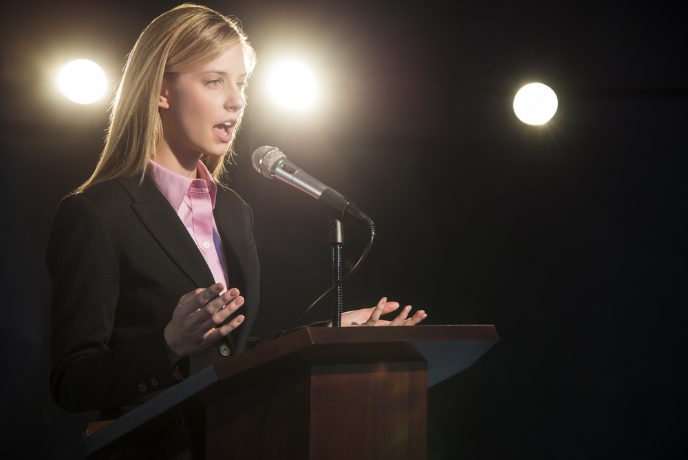 young-businesswoman-giving-speech-podium-auditorium